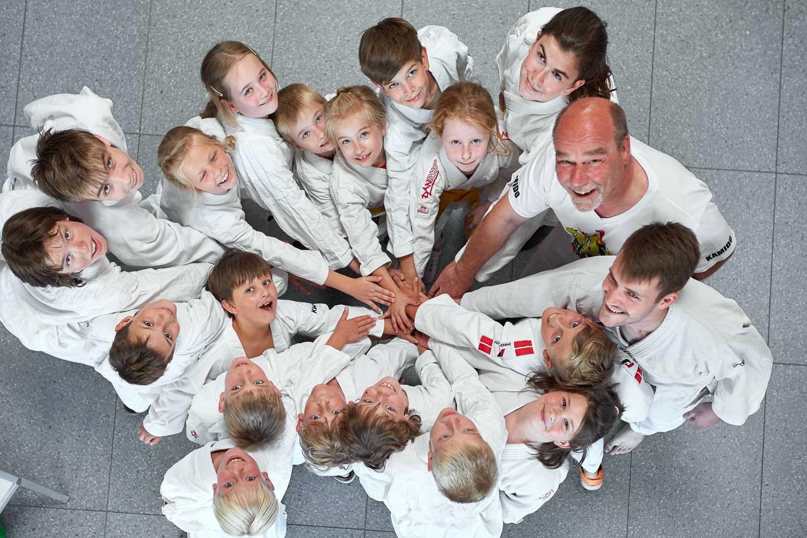 Vereinsmitglieder bilden einen Kreis und legen Hände zusammen